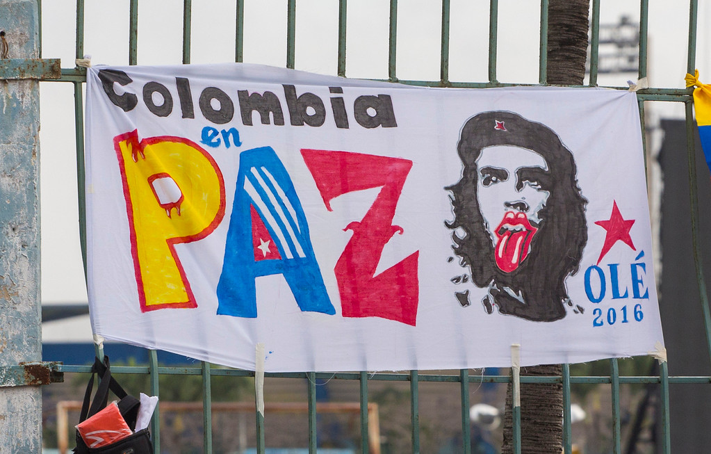 """. A sign that reads in Spanish \""""Colombia in peace\"""" next to Ernesto \""""Che\"""" Guevara with the traditional Rolling Stones tongue hangs on the fence surrounding the venue where the Rolling Stones will play their concert in Havana, Cuba, Friday, March 25, 2016. The Stones are performing in a free concert in Havana Friday, becoming the most famous act to play Cuba since its 1959 revolution.(AP Photo/Desmond Boylan)"""