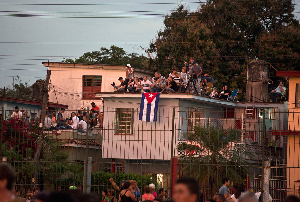 . Fans and media stand on the roof of a house adjacent to the Ciudad Deportiva to get a view of the Rolling Stones concert in Havana, Cuba, Friday March 25, 2016. The Stones are performing in a free concert in Havana Friday, becoming the most famous act to play Cuba since its 1959 revolution. (AP Photo/Desmond Boylan)