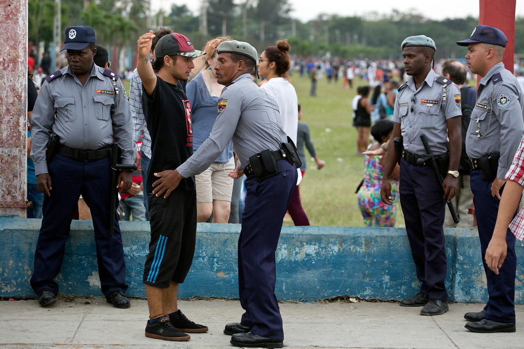 . A spectator is searched by police before entering the venue for a Rolling Stones concert in Havana, Cuba, Friday March 25, 2016. The Stones are performing in a free concert in Havana Friday, becoming the most famous act to play Cuba since its 1959 revolution. (AP Photo/Desmond Boylan)