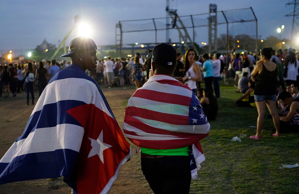 . Fans carrying the Cuban and the U.S. flags draped on their backs arrive at the Ciudad Deportiva for the Rolling Stones concert in Havana, Cuba, Friday March 25, 2016. The Stones are performing in a free concert in Havana Friday, becoming the most famous act to play Cuba since its 1959 revolution. (AP Photo/Ramon Espinosa)