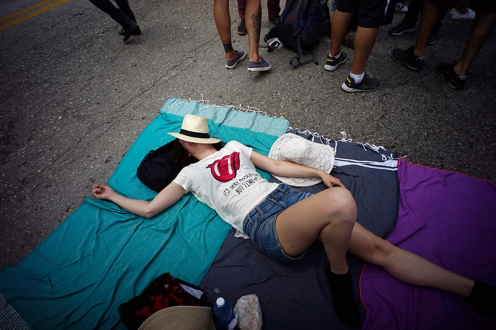 . A fan lies on the floor as she waits outside the venue where the Rolling Stones will play their concert in Havana, Cuba, Friday, March 25, 2016. The Stones are performing in a free concert in Havana Friday, becoming the most famous act to play Cuba since its 1959 revolution.(AP Photo/Ramon Espinosa)