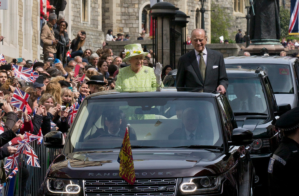 . Britain\'s Queen Elizabeth II (centre L) accompanied by her husband Prince Philip, Duke of Edinburgh greet well-wishers during a \'walkabout\' on her 90th birthday in Windsor, west of London, on April 21, 2016. Britain celebrates Queen Elizabeth II\'s 90th birthday on Thursday, with her eldest son Prince Charles paying tribute in a special radio broadcast and Prime Minister David Cameron leading a parliamentary homage. / AFP PHOTO / JUSTIN TALLIS/AFP/Getty Images