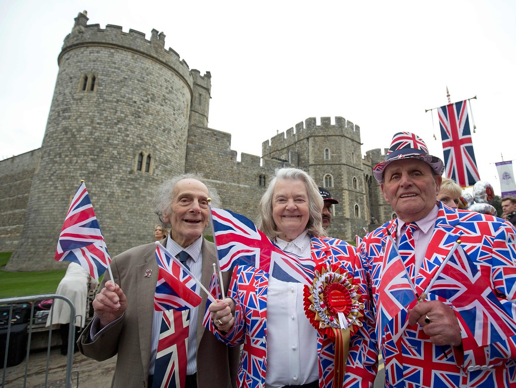 . Royal supporters pose for pictures as they gather outside Windsor Castle, west of London, on April 21, 2016, as Britain\'s Queen Elizabeth II celebrates her 90th birthday. Britain celebrates Queen Elizabeth II\'s 90th birthday on Thursday, with her eldest son Prince Charles paying tribute in a special radio broadcast and Prime Minister David Cameron leading a parliamentary homage. / AFP PHOTO / JUSTIN TALLIS/AFP/Getty Images