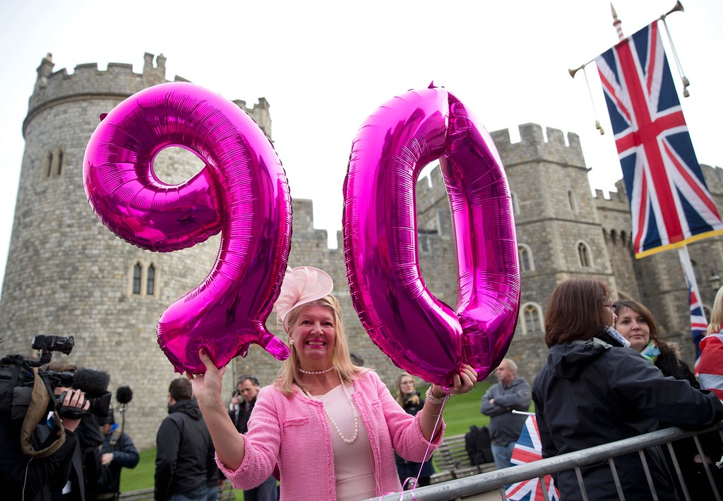 . A royal supporter poses for pictures outside Windsor Castle, west of London, on April 21, 2016, as Britain\'s Queen Elizabeth II celebrates her 90th birthday. Britain celebrates Queen Elizabeth II\'s 90th birthday on Thursday, with her eldest son Prince Charles paying tribute in a special radio broadcast and Prime Minister David Cameron leading a parliamentary homage. / AFP PHOTO / JUSTIN  TALLIS/AFP/Getty Images
