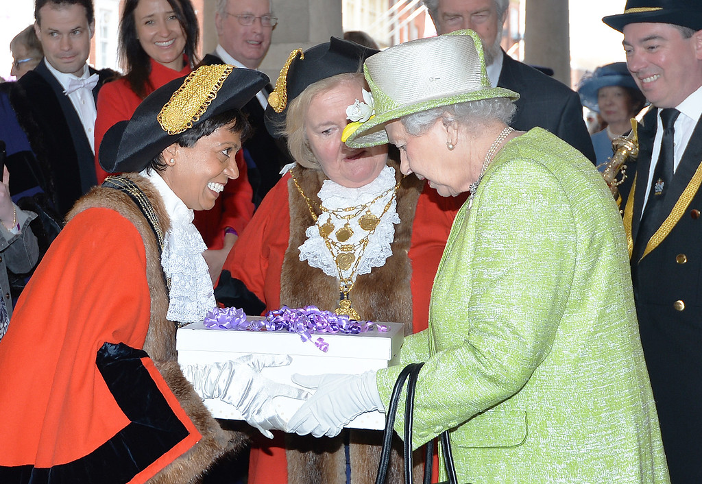 . Britain\'s Queen Elizabeth II is presented with a present during a \'walkabout\' on her 90th birthday in Windsor, west of London, on April 21, 2016.  Britain celebrates Queen Elizabeth II\'s 90th birthday on Thursday, with her eldest son Prince Charles paying tribute in a special radio broadcast and Prime Minister David Cameron leading a parliamentary homage. / AFP PHOTO / POOL / John  STILLWELL/AFP/Getty Images