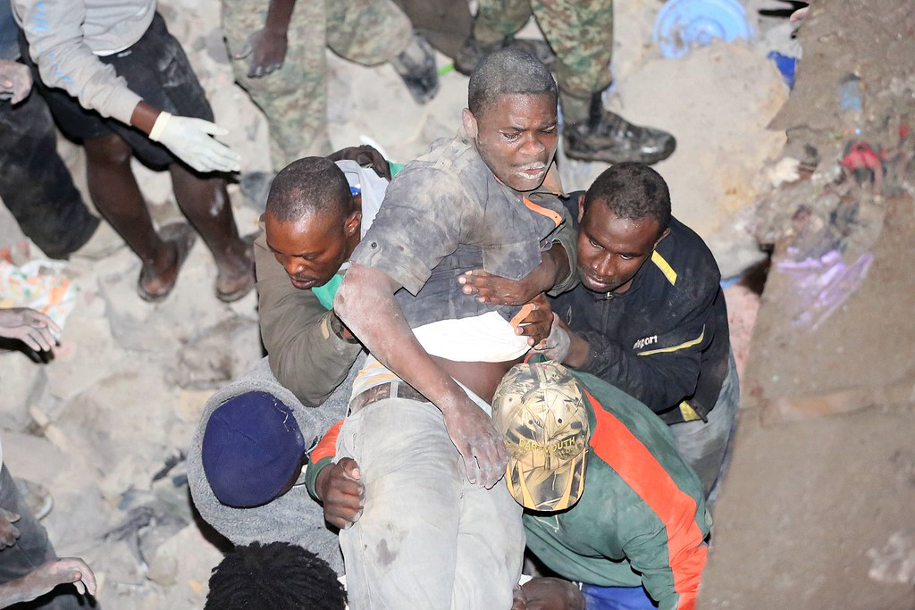. Kenyans carry a survivor rescued from a collapsed building in Nairobi late on April 29, 2016.  / AFP PHOTO / --/AFP/Getty Images