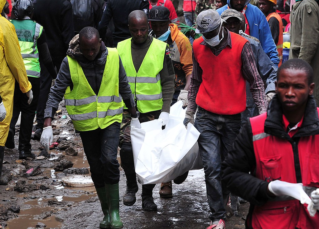 . Kenyan rescue workers carry a body after a building collapsed in Nairobi on April 30, 2016.  / AFP PHOTO / SIMON MAINA/AFP/Getty Images