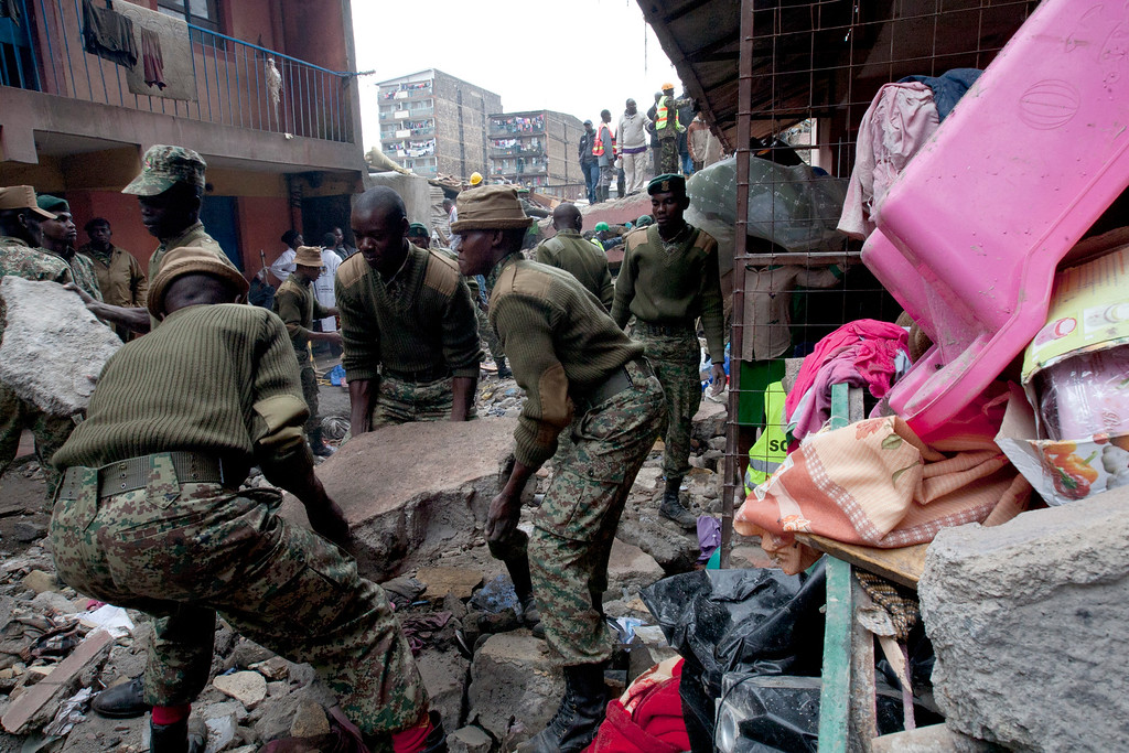 . Personal belongings lie on the right as Kenyan National Youth Service personnel remove stones to make way for large machinery at the site of a building collapse in Nairobi, Kenya, Saturday, April 30, 2016. (AP Photo/Sayyid Abdul Azim)