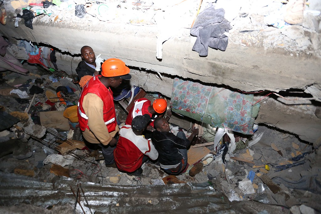 . Emergency personnel try to rescue people trapped under the rubble of a building that collapsed in Nairobi late on April 29, 2016. / AFP PHOTO / --/AFP/Getty Images