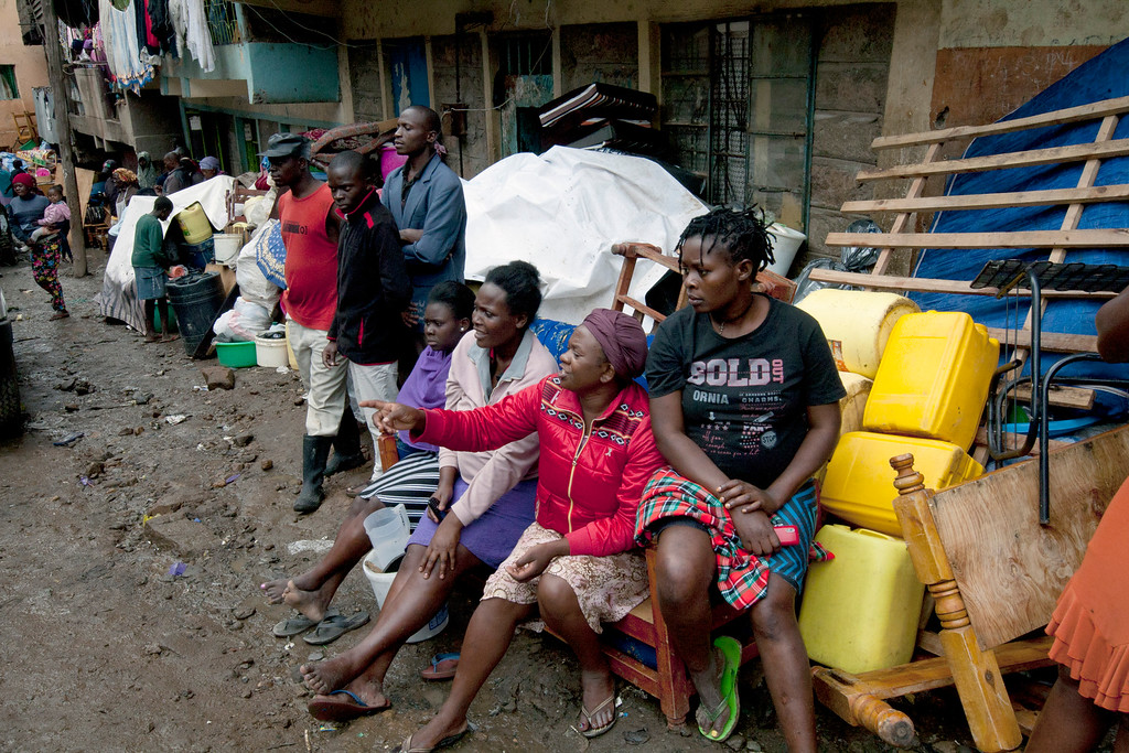 . Survivors sit outside after saving their household items, at the site of a building collapse in Nairobi, Kenya, Saturday, April 30, 2016. A six-story residential building in a low income area of the Kenyan capital collapsed Friday night under heavy rain and flooding, killing at least seven people and injuring over 100 others, Kenyan officials said. (AP Photo/Sayyid Abdul Azim)