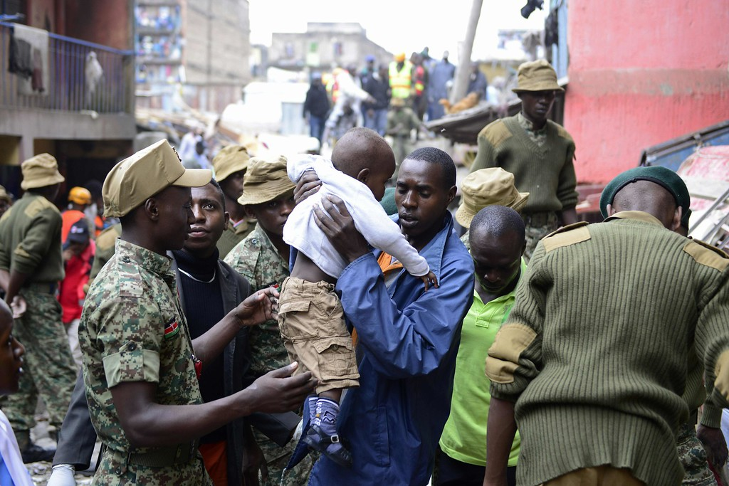 . Kenyan security forces carry a boy as people are evacuated from the vicinity of a collapsed building in Nairobi on April 30, 2016.  / AFP PHOTO / JOHN  MUCHUCHA/AFP/Getty Images