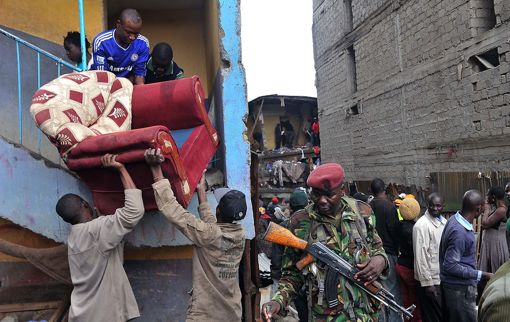 . Residents carry an armchair as they are evacuated after a building collapsed in Nairobi on April 30, 2016. / AFP PHOTO / SIMON MAINASIMON MAINA/AFP/Getty Images