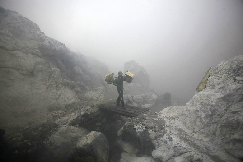 . In this April 16, 2016 photo, a sulfur miner carries baskets full of sulfur slabs through volcanic smoke as he climbs up from the crater of Mount Ijen in Banyuwangi, East Java, Indonesia.  (AP Photo/Binsar Bakkara)