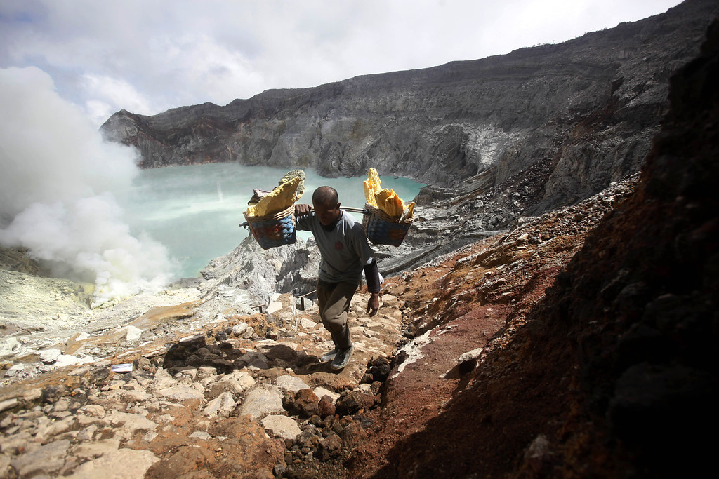 . In this April 16, 2016 photo, Marzuki, a sulfur miner, carries baskets of sulfur as he climbs up from the crater of Mount Ijen in Banyuwangi, East Java, Indonesia. (AP Photo/Binsar Bakkara)