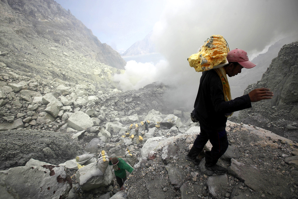 . In this April 16, 2016 photo, a miner tries to balance his steps as he carries sulfur slabs on his shoulders up from the crater of Mount Ijen in Banyuwangi, East Java, Indonesia. (AP Photo/Binsar Bakkara)