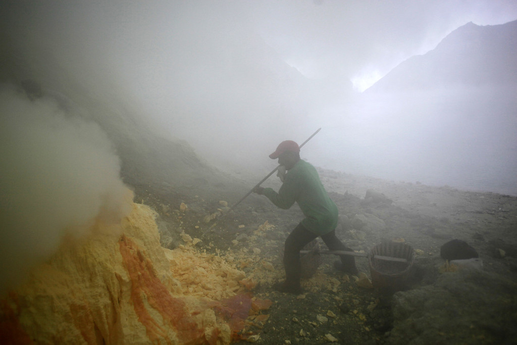 . In this  Saturday, April 16, 2016 photo, a sulfur miner, with only a piece of wet cloth he put in his mouth to protect his respiration, dig out sulfur slabs at the crater of Mount Ijen in Banyuwangi, East Java, Indonesia. Hundreds of  men descend into the volcano�s crater every night to dig out slabs of bright yellow sulfur, enduring toxic fumes and back-breaking loads to earn $10 a day providing a sought-after substance for the fertilizer and cosmetics industries. (AP Photo/Binsar Bakkara)