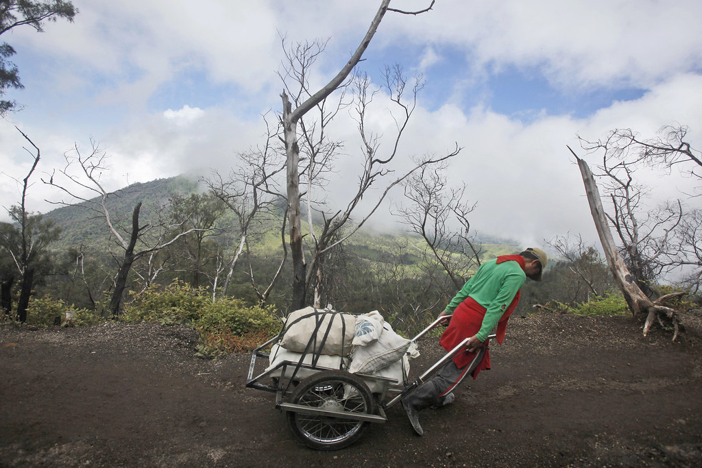 . In this  Saturday, April 16, 2016 photo, a miner pulls a cart fully loaded with sulfur slabs to a collecting point a few kilometers away at Mount Ijen in Banyuwangi, East Java, Indonesia. On average, every miners can make two trips up and down the volcano for a meager earning of Rp. 140.000  (USD 10.6). (AP Photo/Binsar Bakkara)