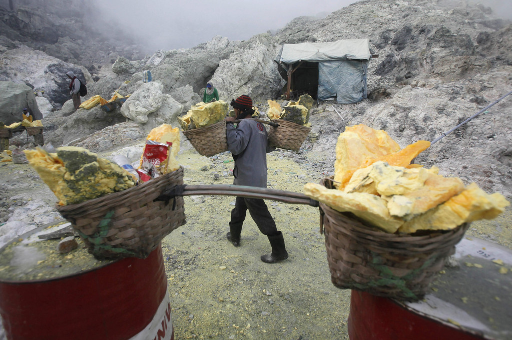 . In this  Saturday, April 16, 2016 photo, a sulfur carries baskets full of sulfur slabs through volcanic smoke as he climb up from the crater of Mount Ijen in Banyuwangi, East Java, Indonesia. The baskets could weigh up to 70 kilograms (154 lbs) which miners have to carry a few kilometers up and on a rocky terrain to a collecting point at the foot of the volcano. (AP Photo/Binsar Bakkara)