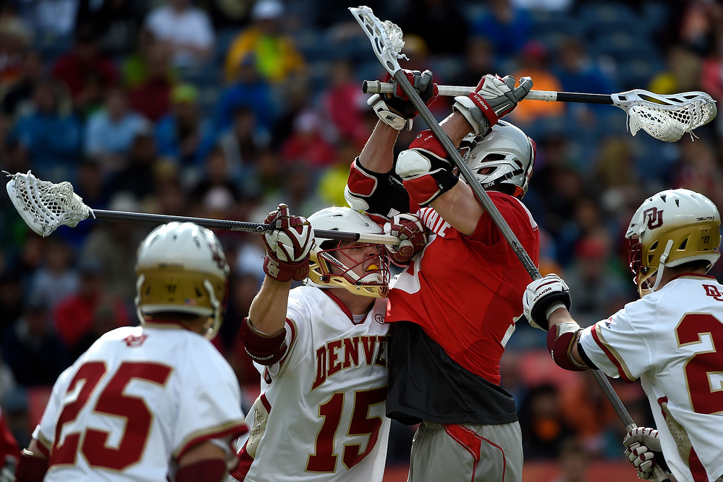 . Christian Burgdorf (15) of the Denver Pioneers hits  Jesse King (19) of the Ohio State Buckeyes during the first half of their NCAA tournament quarterfinal match. The Denver Pioneers played the Ohio State Buckeyes at Sports Authority field at Mile High on Saturday, May 16, 2015. (Photo by AAron Ontiveroz/The Denver Post)