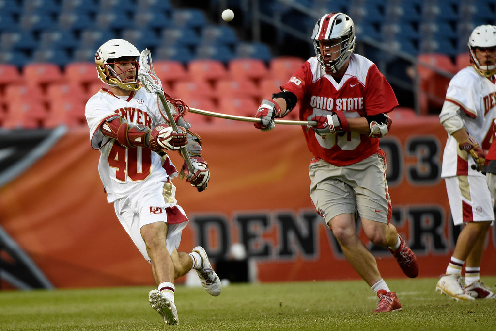 . Connor Cannizzaro (40) of the Denver Pioneers passes as  Robby Haus (50) of the Ohio State Buckeyes pursues during the second half of Denver\'s 15-13 NCAA tournament quarterfinal win. The Denver Pioneers played the Ohio State Buckeyes at Sports Authority field at Mile High on Saturday, May 16, 2015. (Photo by AAron Ontiveroz/The Denver Post)