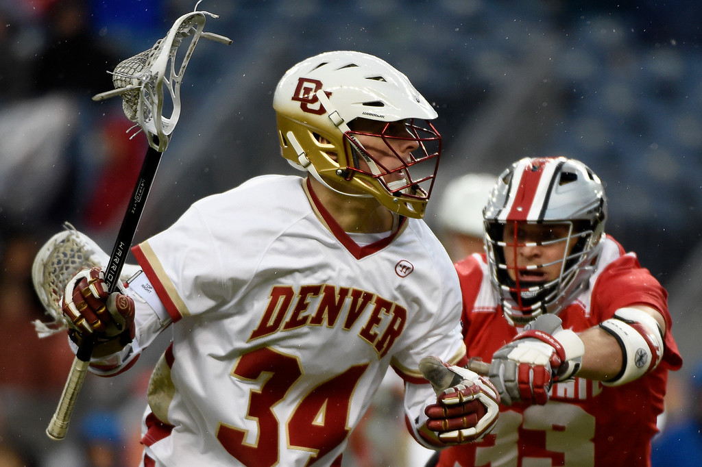 . Erik Adamson (34) of the Denver Pioneers controls the ball as  Kacy Kapinos (33) of the Ohio State Buckeyes defends during the second half of Denver\'s 15-13 NCAA tournament quarterfinal win. The Denver Pioneers played the Ohio State Buckeyes at Sports Authority field at Mile High on Saturday, May 16, 2015. (Photo by AAron Ontiveroz/The Denver Post)