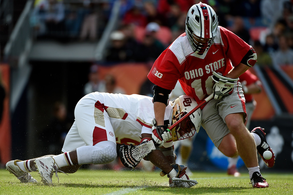 . Jake Withers (18) of the Ohio State Buckeyes and  Trevor Baptiste (9) of the Denver Pioneers battle for a face off during the first half of their NCAA tournament quarterfinal match. The Denver Pioneers played the Ohio State Buckeyes at Sports Authority field at Mile High on Saturday, May 16, 2015. (Photo by AAron Ontiveroz/The Denver Post)
