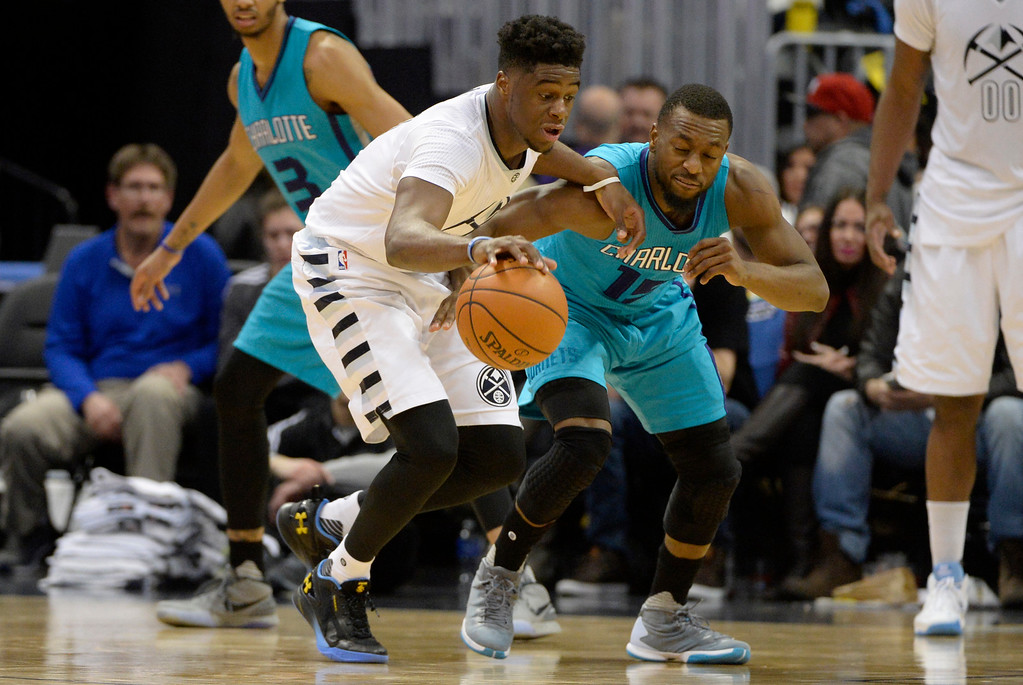 . Kemba Walker (15) of the Charlotte Hornets defends Emmanuel Mudiay (0) of the Denver Nuggets during the fourth quarter of the Nuggets\' 95-92 win. The Denver Nuggets hosted the Charlotte Hornets at the Pepsi Center on Sunday, January 10, 2016. (Photo by AAron Ontiveroz/The Denver Post)