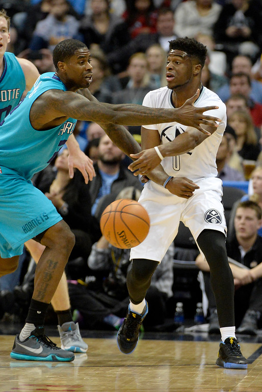 . Emmanuel Mudiay (0) of the Denver Nuggets passes around Marvin Williams (2) of the Charlotte Hornets during the third quarter of the Nuggets\' 95-92 win. The Denver Nuggets hosted the Charlotte Hornets at the Pepsi Center on Sunday, January 10, 2016. (Photo by AAron Ontiveroz/The Denver Post)