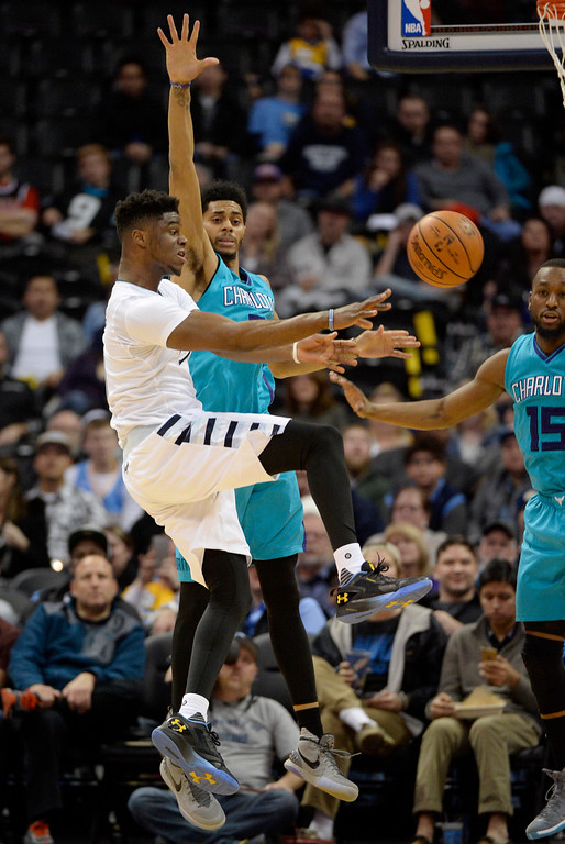 . Emmanuel Mudiay (0) of the Denver Nuggets kicks a pass out as he is defended by Jeremy Lamb (3) of the Charlotte Hornets during the fourth quarter of the Nuggets\' 95-92 win. The Denver Nuggets hosted the Charlotte Hornets at the Pepsi Center on Sunday, January 10, 2016. (Photo by AAron Ontiveroz/The Denver Post)