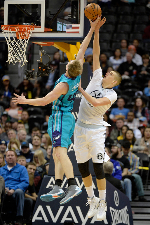 . Nikola Jokic (15) of the Denver Nuggets swats Cody Zeller (40) of the Charlotte Hornets during the third quarter of the Nuggets\' 95-92 win. The Denver Nuggets hosted the Charlotte Hornets at the Pepsi Center on Sunday, January 10, 2016. (Photo by AAron Ontiveroz/The Denver Post)