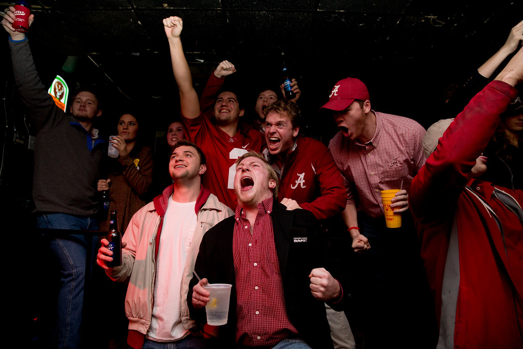 . Alabama fans, Joe Kazoiw, center, 22, of Atlanta, Bruce Gurnowski, left, 21, of Newark, N.J., Zach Soto, back left, 21, of Hoover, Ala., and Mark Smith, back right, 22, of Indianapolis, Ind., cheer after a touchdown during the NCAA college playoff championship football game between Alabama and Clemson at at Gallettes Bar on, Monday, Jan. 11, 2016, in Tuscaloosa, Ala. (AP Photo/Brynn Anderson)