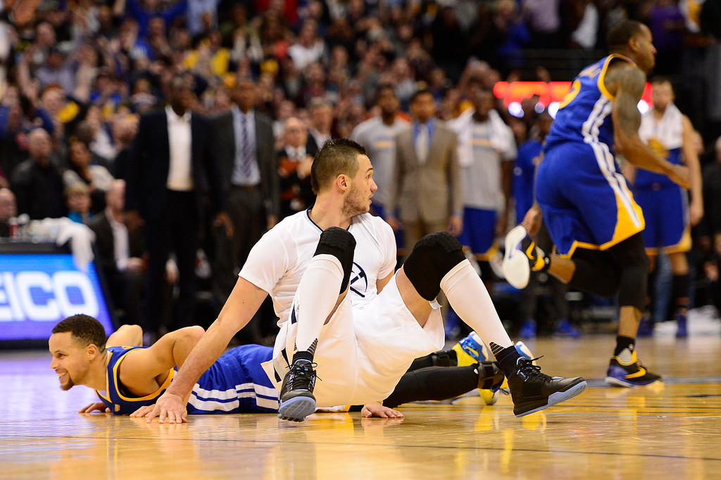 . DENVER, CO - JANUARY 13: Danilo Gallinari (8) of the Denver Nuggets sits next to Stephen Curry (30) of the Golden State Warriors after retrieving a loose ball that brought the Denver Nuggets two points over the Golden State Warriors during the fourth quarter at the Pepsi Center on January 13, 2016 in Denver, Colorado. The Nuggets defeated the Warriors 112-110, giving the Warriors their third loss of the season. (Photo by Brent Lewis/The Denver Post)