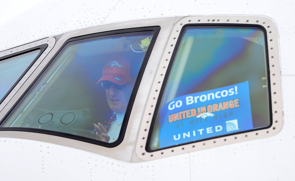 . DENVER, CO - JAN 31: Wearing a Denver Broncos hat, the United pilot prepares the plane for take off. The Denver Broncos depart Denver International Airport on Sunday, Jan. 31, 2016 destined for San Jose, CA. where the team will begin preparations for Super Bowl 50 on Feb. 7, 2016.(Photo by Kathryn Scott Osler/The Denver Post)