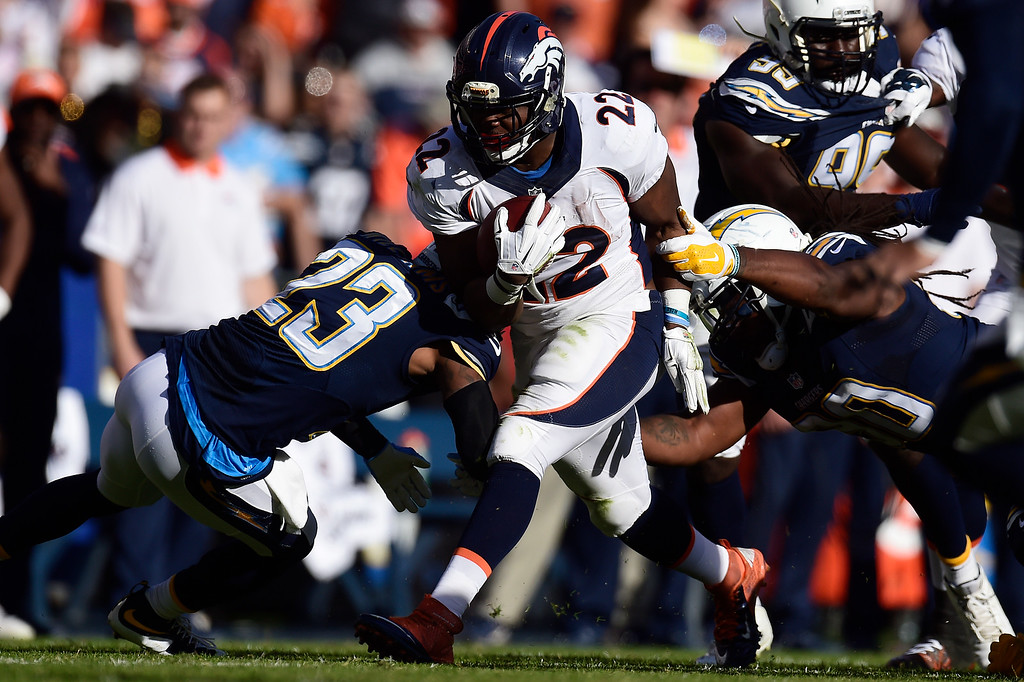 . C.J. Anderson (22) of the Denver Broncos runs as Steve Williams (23) of the San Diego Chargers lays a hit during the first half of the Broncos\' 17-3 win at Qualcom Stadium. The Denver Broncos played the San Diego Chargers in a week 13 NFL game on Sunday, December 6, 2015. (Photo by AAron Ontiveroz/The Denver Post)