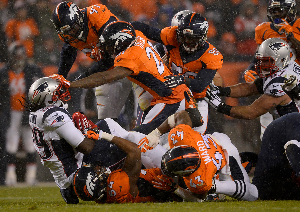 . New England Patriots running back LeGarrette Blount (29) gets shoved by Denver Broncos cornerback Aqib Talib (21) for a loss during the first quarter November 29, 2015 at Sports Authority Field at Mile High Stadium. (Photo By Helen H. Richardson/The Denver Post)