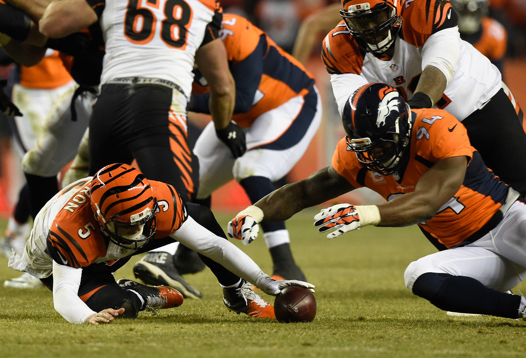 . DENVER, CO - DECEMBER 28: Cincinnati Bengals quarterback AJ McCarron (5) and Denver Broncos outside linebacker DeMarcus Ware (94) dive after the loose ball after mishandling the nap in overtime December 28, 2015 at Sports Authority Field at Mile High Stadium. Denver Broncos outside linebacker DeMarcus Ware (94) recovered the loose ball to secure the victory 20-17. (Photo By Helen Richardson/The Denver Post)