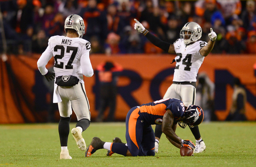 . DENVER, CO - DECEMBER 13: Oakland Raiders free safety Charles Woodson (24) celebrates with Oakland Raiders strong safety Taylor Mays (27) after Denver Broncos tight end Vernon Davis (80) dropped a pass with 3:50 left in the game  December 13, 2015 at Sports Authority Field at Mile High Stadium. (Photo By Eric Lutzens/The Denver Post)