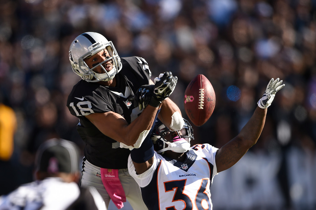 . Kayvon Webster #36 of the Denver Broncos knocks the ball away from Andre Holmes #18 of the Oakland Raiders at O.Co Coliseum in Oakland, Calif., October 11, 2015. (Photo By Joe Amon/The Denver Post)
