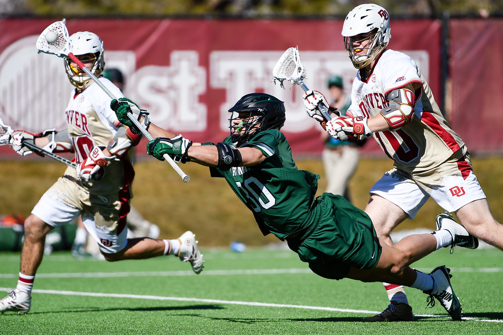 . DENVER, CO - FEBRUARY 28: Dartmouth Austin Meacham (30) ,makes a pass while falling down in front of Denver Colton Jackson (10) during the Face-off Classic February 28, 2016 at Peter Barton Lacrosse Stadium. (Photo By John Leyba/The Denver Post)