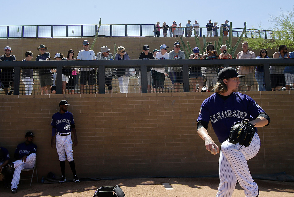 . Fans watch as Colorado Rockies starting pitcher Jon Gray throws in the bullpen before a spring training baseball game between the Rockies and the Milwaukee Brewers in Scottsdale, Ariz., Tuesday, March 22, 2016. (AP Photo/Jeff Chiu)