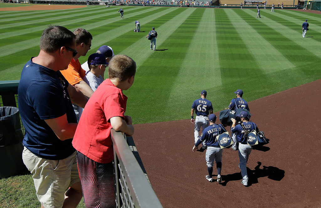 . Fans watch as Milwaukee Brewers arrive before a spring training baseball game between the Colorado Rockies and the Brewers in Scottsdale, Ariz., Tuesday, March 22, 2016. (AP Photo/Jeff Chiu)