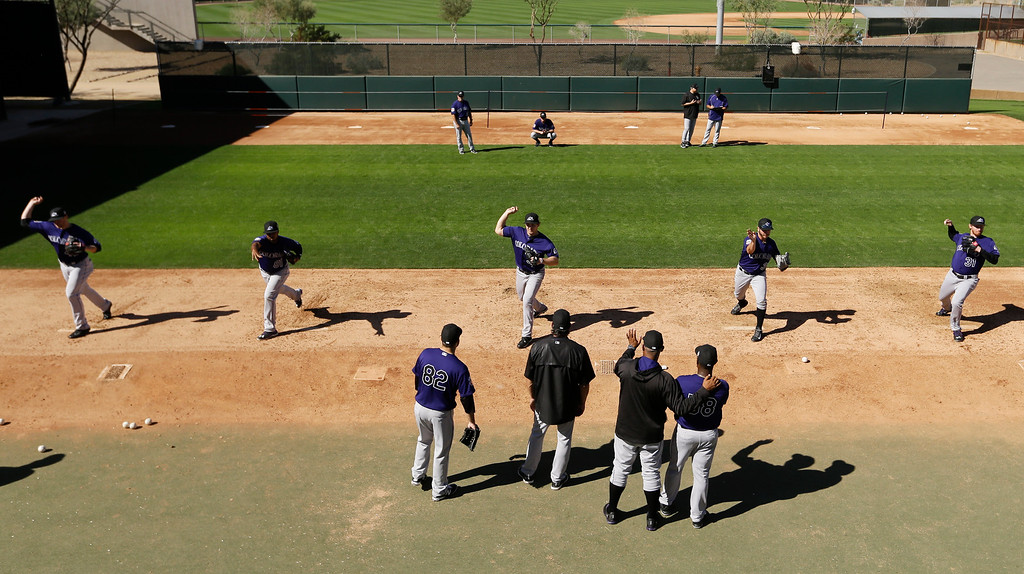 . Members of the Colorado Rockies pitching staff work on drills during spring training baseball practice in Scottsdale, Ariz., Monday, Feb. 22, 2016. (AP Photo/Chris Carlson)