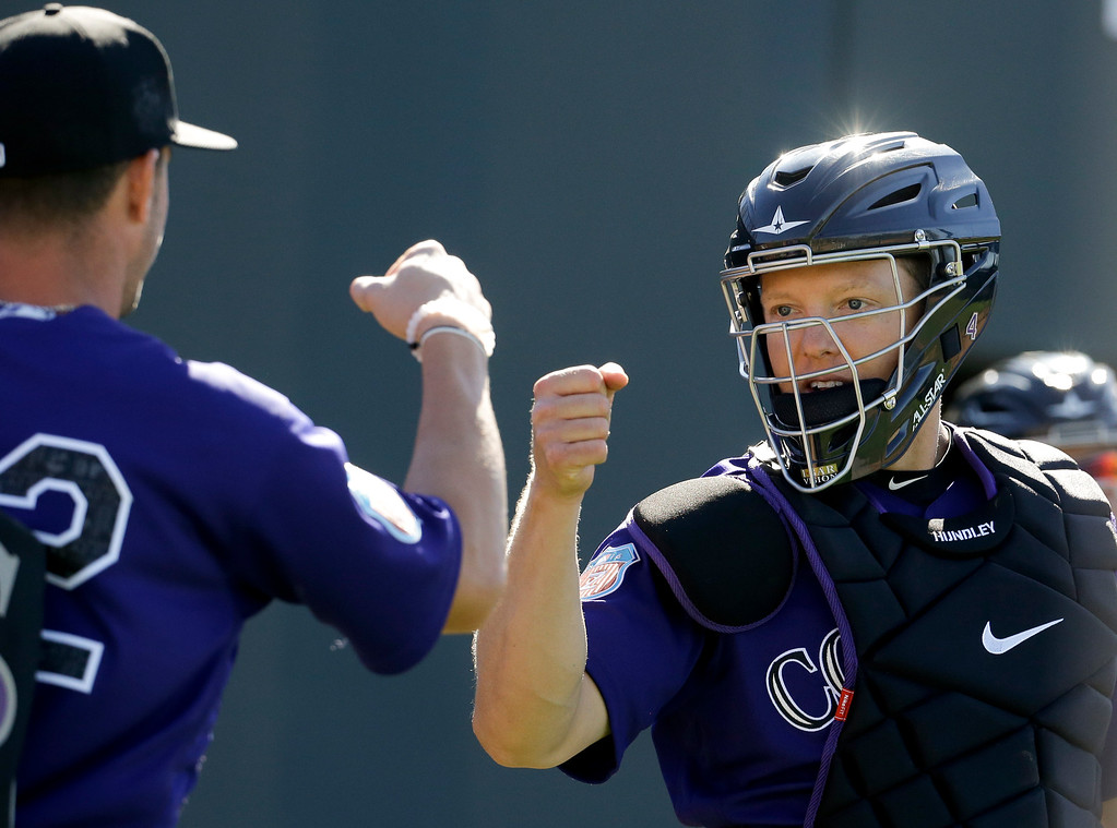 . Colorado Rockies catcher Nick Hundley, right, greets starting pitcher Chris Rusin during spring training baseball practice in Scottsdale, Ariz., Monday, Feb. 22, 2016. (AP Photo/Chris Carlson)