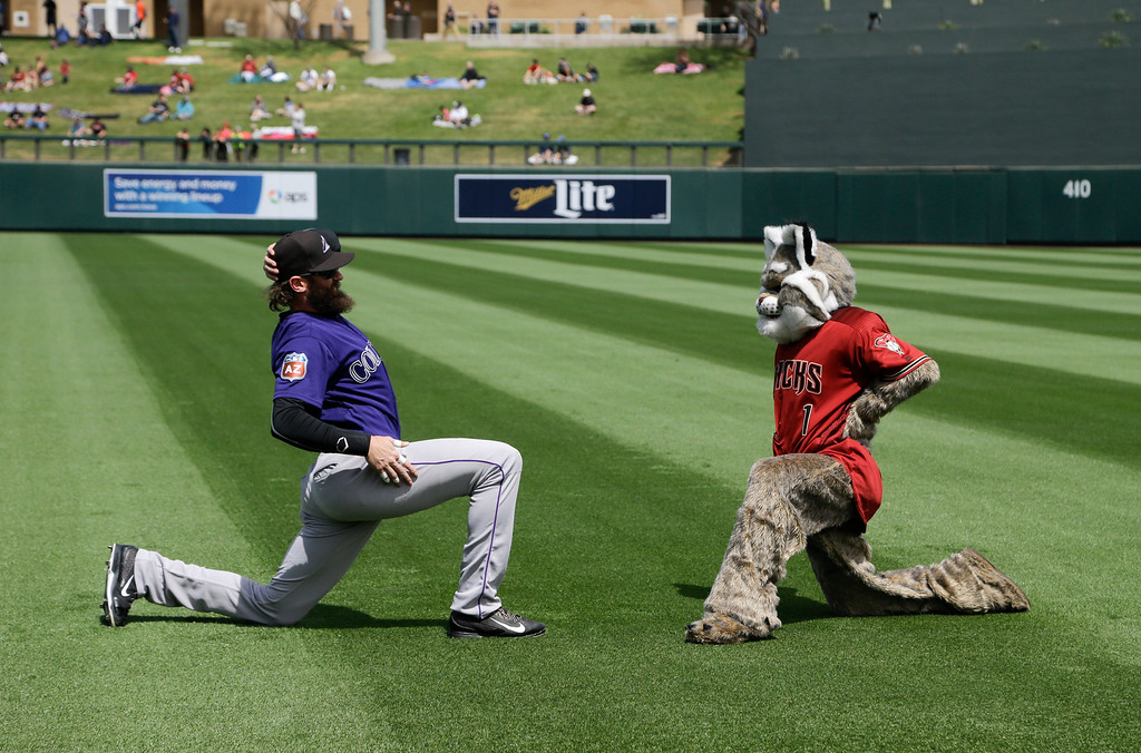 . Arizona Diamondbacks mascot Baxter, right, jokingly stretches in front of Colorado Rockies\' Charlie Blackmon before a spring training baseball game Tuesday, March 29, 2016, in Scottsdale, Ariz. (AP Photo/Jae C. Hong)