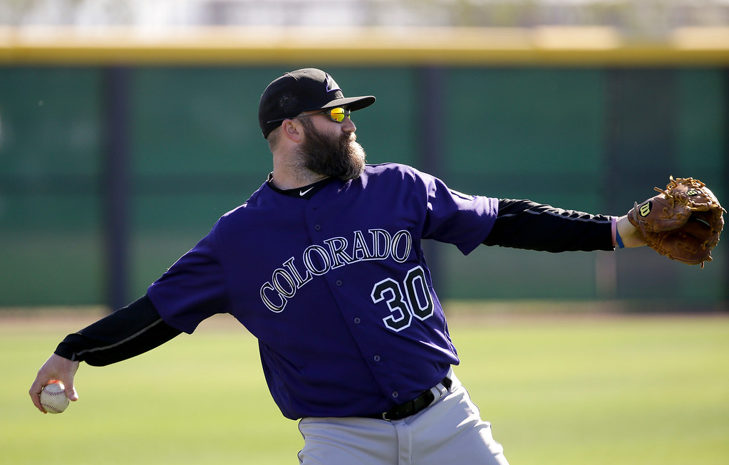 . Colorado Rockies relief pitcher Jason Motte throws during spring training baseball practice in Scottsdale, Ariz., Monday, Feb. 22, 2016. (AP Photo/Chris Carlson)