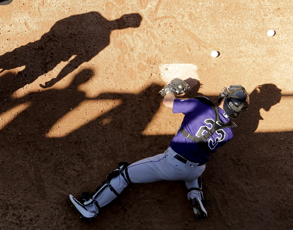 . Colorado Rockies catcher Tom Murphy reaches for a ball during spring training baseball practice in Scottsdale, Ariz., Monday, Feb. 22, 2016. (AP Photo/Chris Carlson)