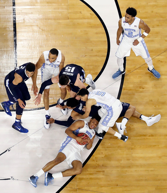 . North Carolina\'s Kennedy Meeks grabs a loose ball as he falls during the second half of the NCAA Final Four tournament college basketball championship game against Villanova, Monday, April 4, 2016, in Houston. (AP Photo/Michael Simmons)
