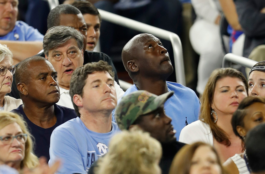 . Former North Carolina and NBA basketball player and principal owner and chairman of the Charlotte Hornets Michael Jordan watches the scoreboard during the first half of the NCAA Final Four tournament college basketball championship game between Villanova and North Carolina, Monday, April 4, 2016, in Houston. (AP Photo/David J. Phillip)
