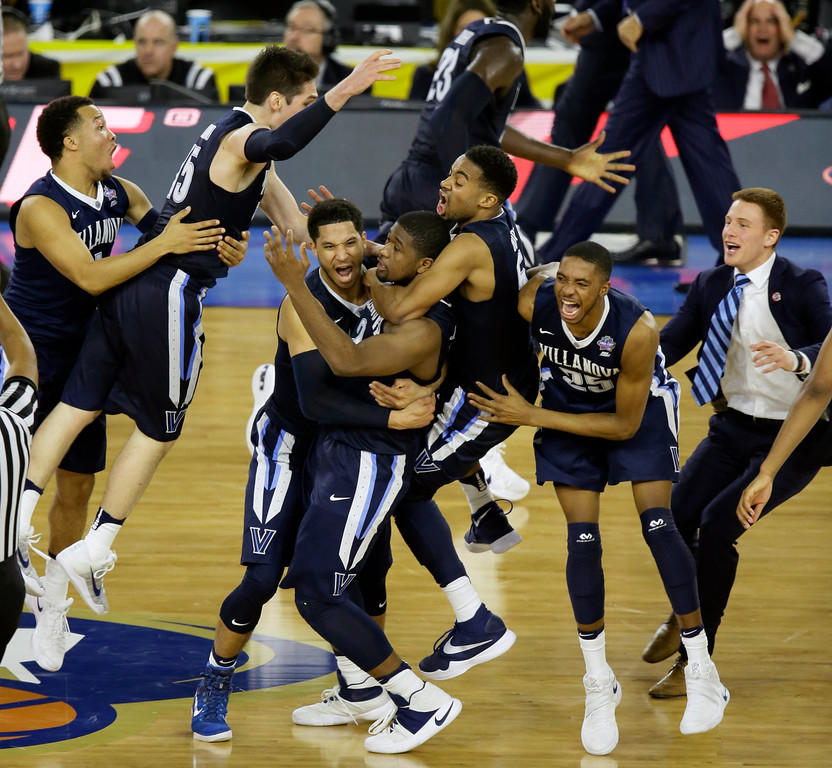 . Villanova players celebrates after Kris Jenkins, center, scores a game winning three point basket in the closing seconds of NCAA Final Four tournament college basketball championship game Monday, April 4, 2016, in Houston. Villanova won 77-74. (AP Photo/Charlie Neibergall)
