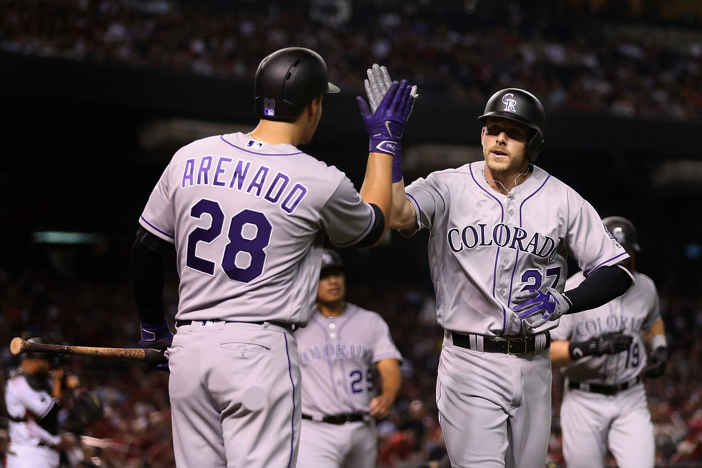 . PHOENIX, AZ - APRIL 04:  Trevor Story #27 of the Colorado Rockies high fives Nolan Arenado #28 after Story hit a three run home-run against the Arizona Diamondbacks during the third inning of the MLB opening day game at Chase Field on April 4, 2016 in Phoenix, Arizona.  (Photo by Christian Petersen/Getty Images)